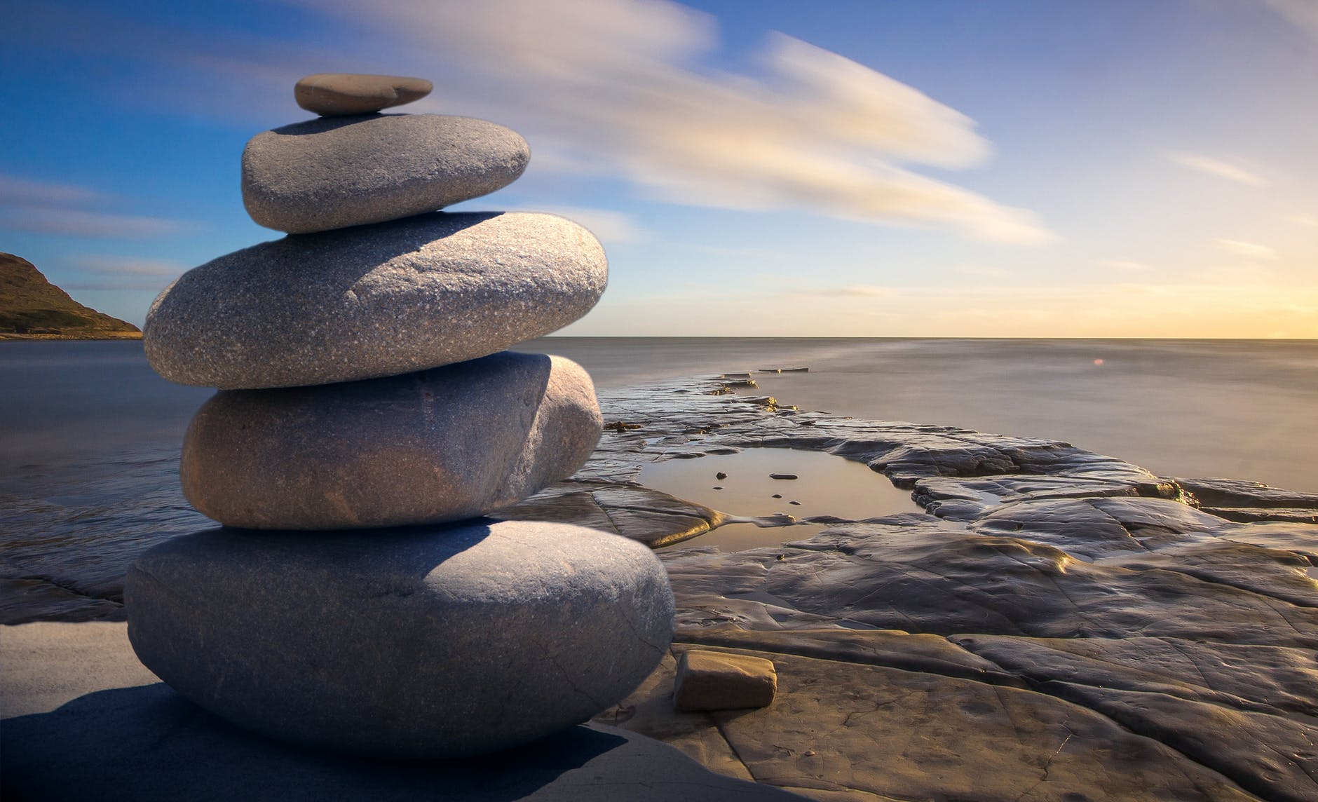 Stones stacked on top of one another to form a tower near an ocean shore