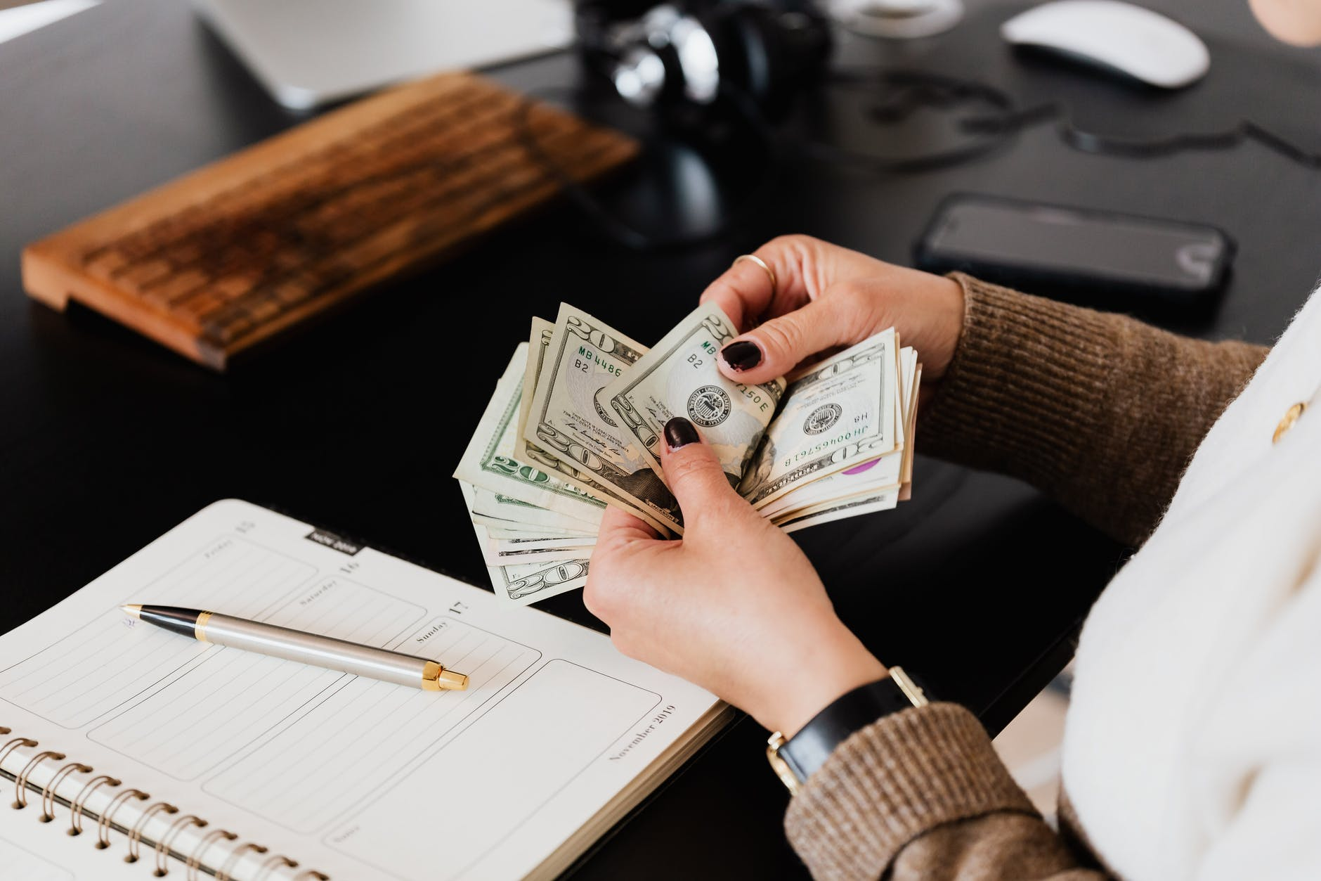 Woman counting several twenty dollar bills in her hands